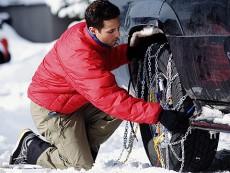 Homem montando correntes de neve